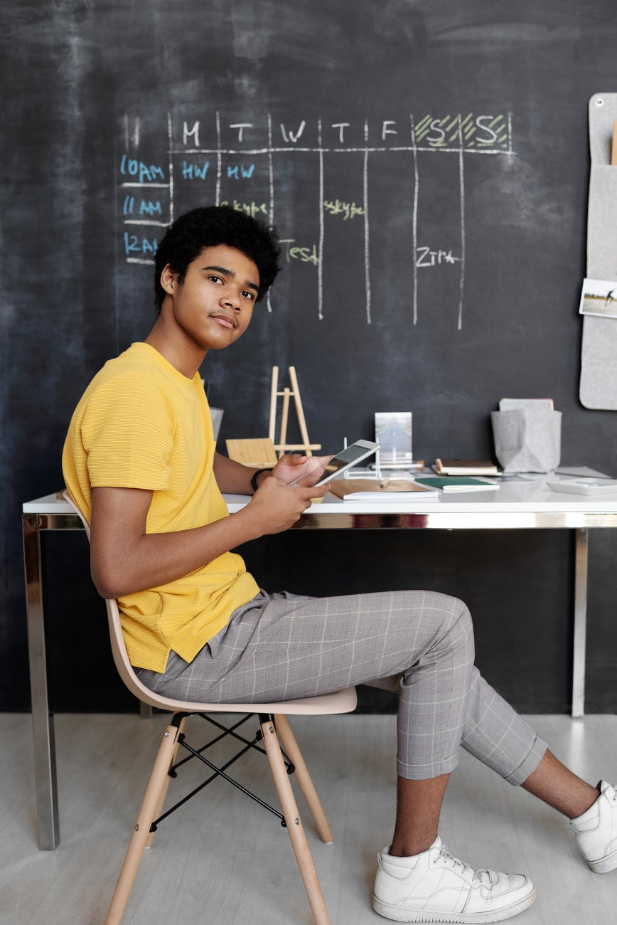 photo of boy sitting on chair while holding an ipad