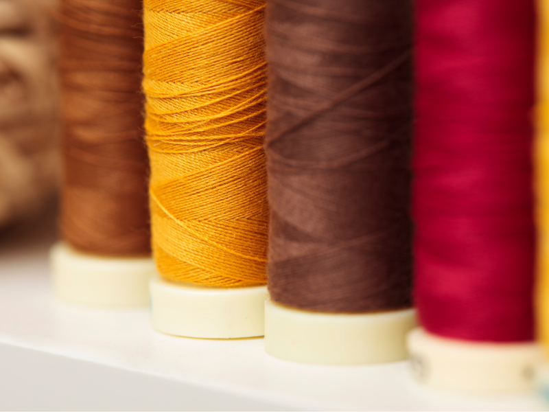 Large spools of thread in brown, yellow and red