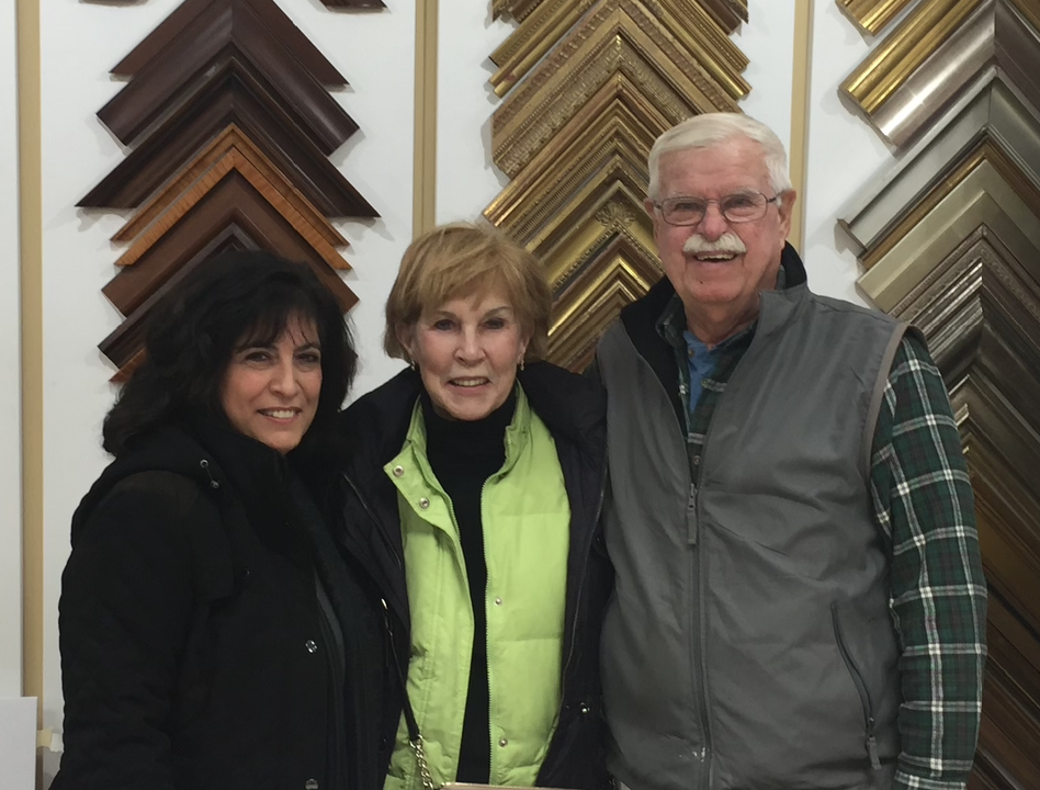 LuAnn, Pat and Bruce standing in front of picture framing corner samples