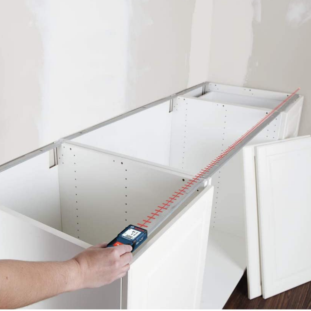 Using a laser tape measure to measure a cabinet