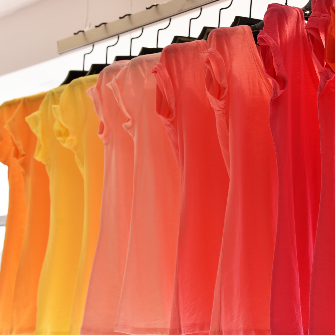 T shirts hanging on rack in colors from red, pink, yellow and orange