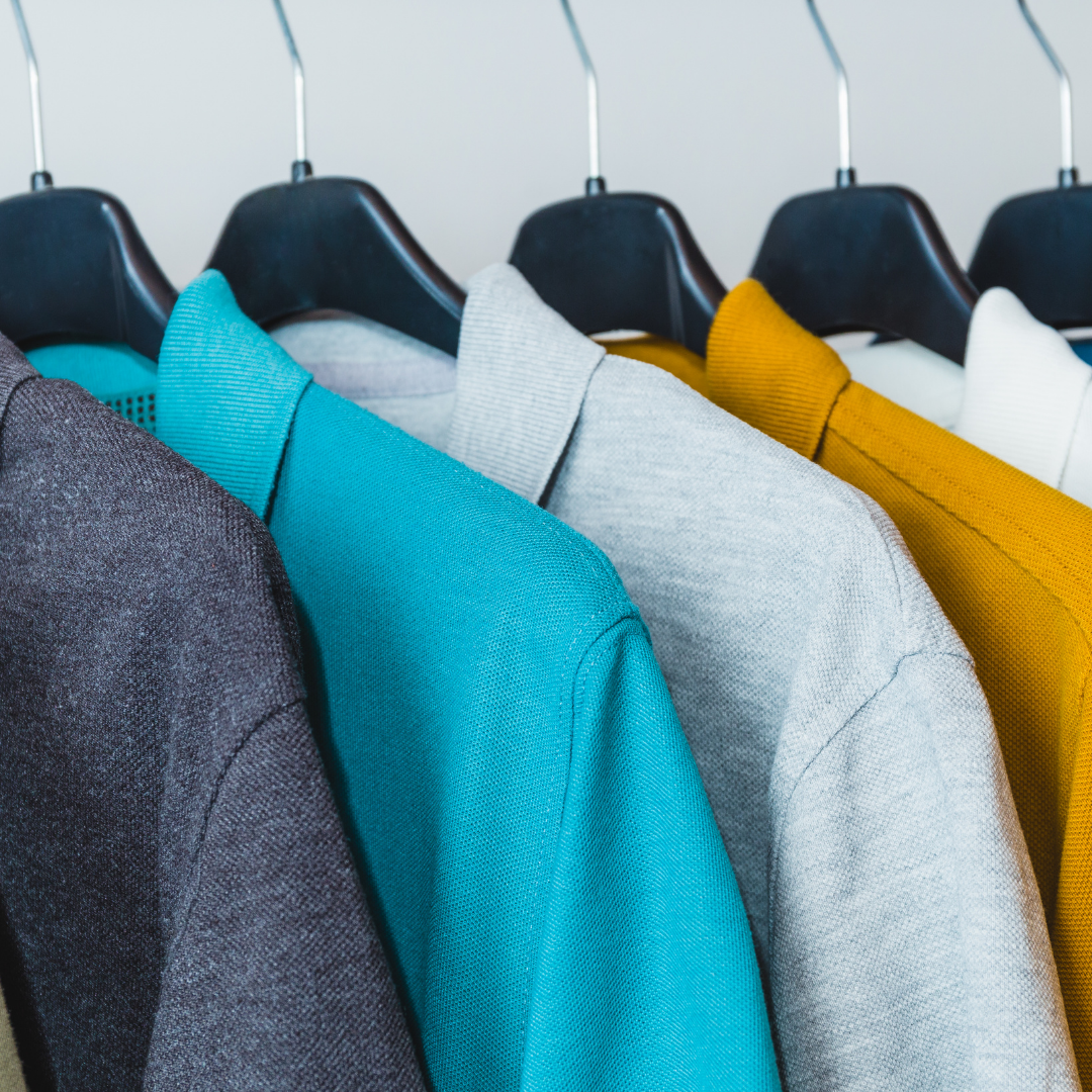Polo shirts in gray, blue and gold hanging on rack