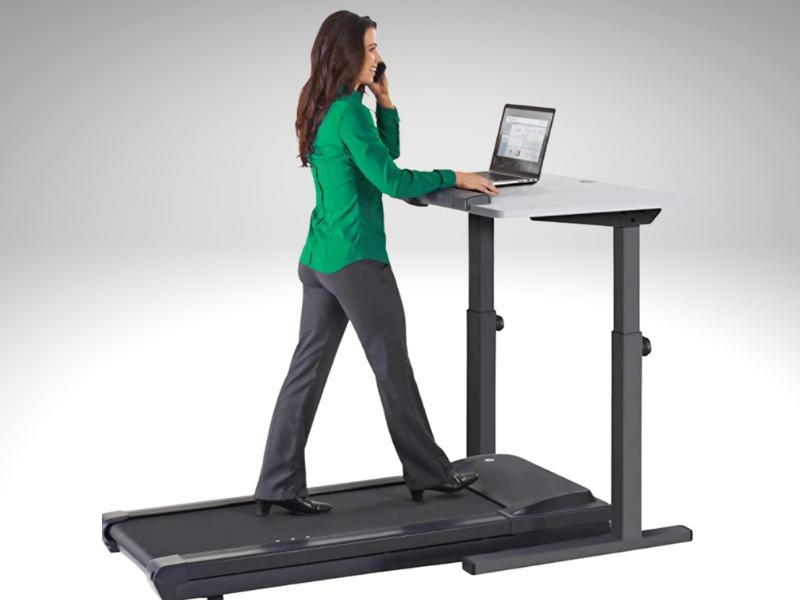 Woman walking on treadmill desk while talking on phone