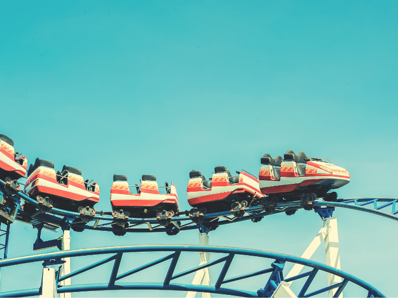 Roller coaster going down hill with blue sky in background